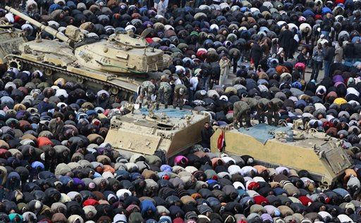 Anti-government protesters, and Egyptian soldiers on top of their vehicles, make traditional Muslim Friday prayers at the continuing demonstration in Tahrir Square in downtown Cairo, Egypt Friday, Feb. 11, 2011. &#40;AP Photo&#47;Ben Curtis&#41; <span class=meta>(AP Photo&#47; Ben Curtis)</span>