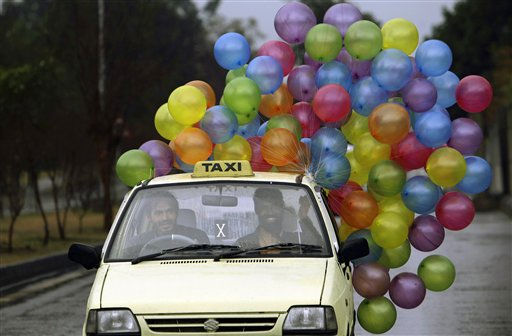 A Pakistani vendor holds his balloons while sitting in a Taxi driving along a road in preparation for Valentine&#39;s Day in Islamabad, Pakistan, Sunday, Feb. 13, 2011. &#40;AP Photo&#47;Muhammed Muheisen&#41; <span class=meta>(AP Photo&#47; Muhammed Muheisen)</span>