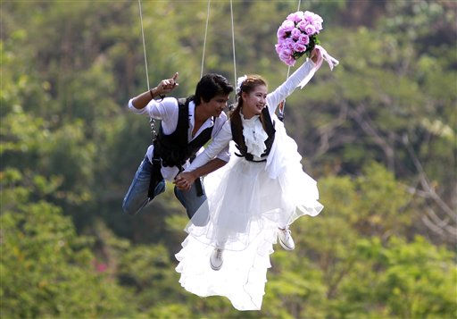 Sontaya Tiemjun, left, and Praputson Mahavong, right, swing out on rappelling ropes during their wedding ceremony Sunday, Feb. 13, 2011 in Prachinburi province, Thailand.  The mountainside ceremony has become a favorite of adventure seeking Thai couples looking to marry near or on Valentine&#39;s Day.  &#40;AP Photo&#47;Wason Wanichakorn&#41; <span class=meta>(AP Photo&#47; Wason Wanichakorn)</span>