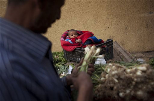 "<div class=""meta ""><span class=""caption-text "">A man prepares vegetables to be sold as his baby rests on a crate in a fruits and vegetables stall in a market in downtown Cairo, Egypt, Monday, Feb. 14, 2011. Egypt's military rulers dissolved parliament Sunday, suspending the constitution and promising elections in moves cautiously welcomed by pro-democracy protesters. (AP Photo/Emilio Morenatti) (AP Photo/ Emilio Morenatti)</span></div>"
