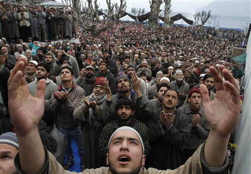 Kashmiri Muslims raise their hands for prayers as head priest displays a relic of Prophet Mohammed, unseen, to mark the birth anniversary of the Prophet at the Hazratbal Shrine in Srinagar, India, Wednesday, Feb. 16, 2011. Thousands of Kashmiri Muslims gathered at the Hazratbal shrine, which houses a relic believed to be a hair from the beard of the Prophet, to offer prayers on his birth anniversary. &#40;AP Photo&#47;Mukhtar Khan&#41; <span class=meta>(AP Photo&#47; Mukhtar Khan)</span>