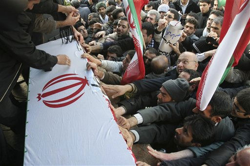 Pro-government Iranians touch the flag-draped coffin of Sane Jaleh, a student who was killed during Monday&#39;s clashes, during a funeral ceremony in Tehran, Iran, Wednesday, Feb. 16, 2011. Iran&#39;s state TV described Jaleh a government supporter and a member of the paramilitary Basij, part of the Guard forces that have cracked down on protesters. But the reformist website kaleme.com called him a member of election campaign of opposition leader Mir Hossein Mousavi. Clashes between Iranian police and tens of thousands of protesters wracked central Tehran on Monday killing one person, as opposition supporters tried to evoke the spirit of Egypt&#39;s recent popular uprising. &#40;AP Photo&#41; <span class=meta>(AP Photo&#47; Anonymous)</span>