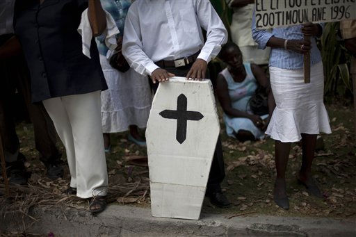 Relatives of children who died after ingesting cough syrup in 1995 protest holding a fake coffin as they demand compensation from Haitian courts in Port-au-Prince, Haiti, Thursday Feb. 17, 2011.  Nearly 90 children died in Haiti after they ingested a cheap cough syrup laced with a chemical used in antifreeze. &#40;AP Photo&#47;Ramon Espinosa&#41; <span class=meta>(AP Photo&#47; Ramon Espinosa)</span>