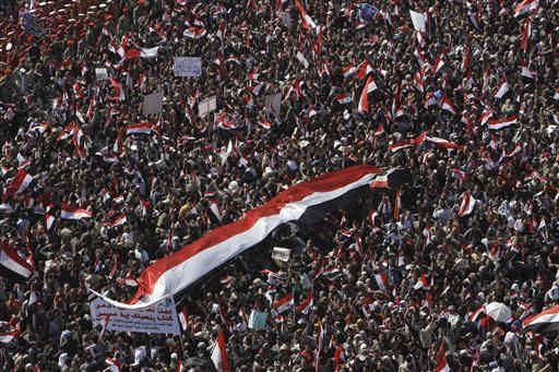 People carry an Egyptian flag as they arrive to attend Friday prayers and a demonstration in Tahrir Square in Cairo, Egypt, Friday Feb. 18, 2011. Protests continued and labor unrest has increased in Egypt since President Hosni Mubarak&#39;s departure last week that set off a chain reaction around the Middle East, with anti-government demonstrations reported in Libya, Bahrain and Yemen.&#40;AP Photo&#47;Hussein Malla&#41; <span class=meta>(AP Photo&#47; Hussein Malla)</span>