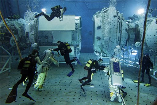 Trainees in spacesuits assisted by scuba divers train in a pool at the Russian Cosmonauts Training Center at the Star City outside Moscow, Friday, Feb. 18, 2011. Underwater training simulating conditions of weightlessness is part of space crew training. &#40;AP Photo&#47;Sergey Ponomarev&#41; <span class=meta>(AP Photo&#47; Sergey Ponomarev)</span>