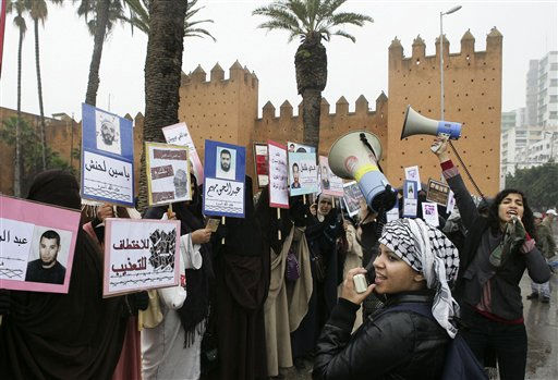 "<div class=""meta ""><span class=""caption-text "">Two women activists shout slogan against the Moroccan government near veiled women holding placards of jailed relatives during a protest in Rabat, Sunday Feb. 20, 2011. At least 2,000 people are marching in Morocco's capital to demand a new constitution that would bring greater democracy in the North African kingdom. Demonstrators shouted slogans calling for economic opportunity, educational reform, better health services and help in coping with rising living costs during the march on central Hassan II Avenue in Rabat. (AP Photo/Abdeljalil Bounhar) (AP Photo/ Abdeljalil Bounhar)</span></div>"