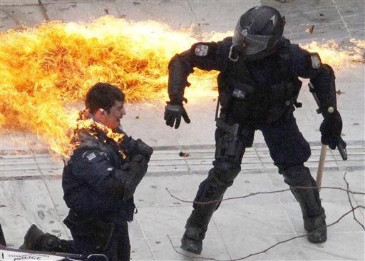 A motorcycle policeman burns as his colleague, left, tries to help him after protesters threw a petrol bomb in Athens, Wednesday, Feb. 23, 2011. Scores of youths hurled rocks and petrol bombs at riot police after clashes broke out Wednesday during a mass rally taking place as part of a general strike. &#40;AP Photo.Dimitri Messinis&#41; <span class=meta>(AP Photo&#47; Dimitri Messinis)</span>