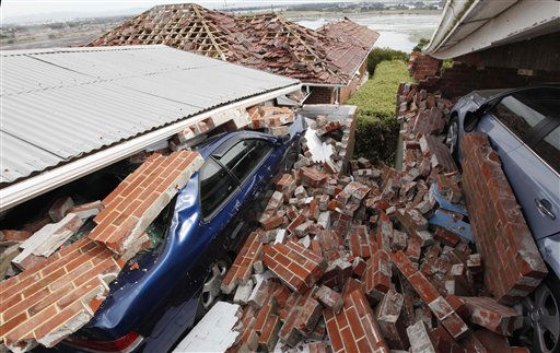 Cars sit crushed under the rubble in a Christchurch suburb following last Tuesday&#39;s magnitude 6.3 temblor in Christchurch, New Zealand, Monday, Feb. 28, 2011. Police said the death toll from the quake had reached 148 and was expected to rise further. Around 200 people are listing as missing, though many are believed to be among bodies already collected but whose identities have not been established. &#40;AP Photo&#47;Mark Baker&#41; <span class=meta>(AP Photo&#47; Mark Baker)</span>
