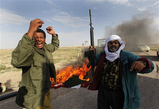 "<div class=""meta image-caption""><div class=""origin-logo origin-image ""><span></span></div><span class=""caption-text"">Libyan rebel celebrate after they retook the town from pro-Gadhafi fighters, in Brega, east of Libya, on Wednesday March 2, 2011. Regime opponents battled forces loyal to Libyan leader Moammar Gadhafi who tried Wednesday to retake a key oil installation in a counteroffensive Wednesday against the rebel-held eastern half of the country. At one point in the flip-flopping battle, anti-Gadhafi fighters cornered the attackers in a nearby seaside university campus in fierce fighting that killed at least five. (AP Photo/Hussein Malla) (AP Photo/ Hussein Malla)</span></div>"