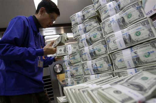 "<div class=""meta ""><span class=""caption-text "">A South Korean bank clerk works next to bundles of U.S. banknotes at the head office of the Korea Exchange Bank in Seoul, South Korea, Thursday, March 3, 2011. South Korea's foreign currency reserves hit a new record high in February for the second straight month, the central bank said Thursday, though the country's global ranking slipped to seventh in total holdings. (AP Photo/ Lee Jin-man) (AP Photo/ Lee Jin-man)</span></div>"