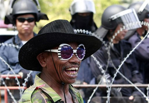 A protester laughs as he is watched by Thai riot police officers during a demonstration outside the government house in Bangkok, Thailand, Tuesday, March 8, 2011. Several hundreds of protesters, most of them farmers from the country&#39;s northeastern part, staged the demonstration urging the government to solve their land reforming problems. &#40;AP Photo&#47;Apichart Weerawong&#41; <span class=meta>(AP Photo&#47; Apichart Weerawong)</span>