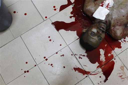 "<div class=""meta ""><span class=""caption-text "">**EDS NOTE: GRAPHIC CONTENT** The body of unidentified man lies where he died, on the corridor floor of a health clinic, after security forces loyal to Laurent Gbagbo open fire on civilians in the Treichville neighborhood of Abidjan, Ivory Coast Tuesday, March 8, 2011. Soldiers backing Ivory Coast's rogue leader opened fire on civilians again Tuesday, killing at least four people hours after hundreds took to the streets to protest the deaths of seven women gunned down at a march last week. (AP Photo/Rebecca Blackwell) (AP Photo/ Rebecca Blackwell)</span></div>"