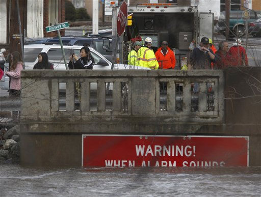 The water level on the Ramapo River covers most of a warning sign as residents look on at an emergency post near the Ramapo River flood gate in Wayne, N.J. on Friday, March 11, 2011. The levels of the river continued to rise as a result of a storm that hit the northern New Jersey region. &#40;AP Photo&#47;Julio Cortez&#41; <span class=meta>(AP Photo&#47; Julio Cortez)</span>