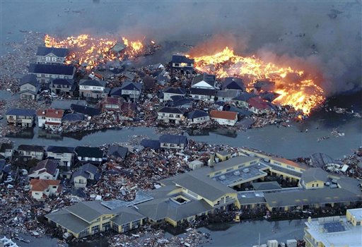 Houses are in flame while the Natori river is flooded over the surrounding area by tsunami tidal waves in Natori city, Miyagi Prefecture, northern Japan, March 11, 2011, after strong earthquakes hit the area. &#40;AP Photo&#47;Yasushi Kanno, The Yomiuri Shimbun&#41;  JAPAN OUT, CREDIT MANDATORY <span class=meta>(AP Photo&#47; Yasushi Kanno)</span>