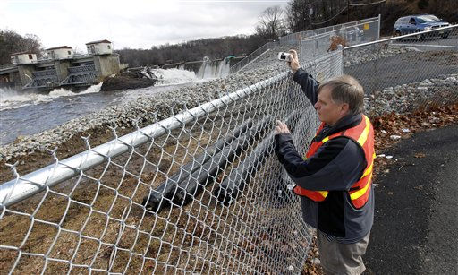 A man uses a camera to photograph the rushing water at the Ramapo River flood gate in Wayne, N.J., as water levels continued to rise following a storm that hit the northern New Jersey area, Friday, March 11, 2011. &#40;AP Photo&#47;Julio Cortez&#41; <span class=meta>(AP Photo&#47; Julio Cortez)</span>