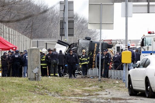 Emergency personnel work at the scene where thirteen people died when a bus returning to New York City from a casino on Saturday, March 12, 2011, overturned on a highway and was sliced in half by the support pole for a large sign. &#40;AP Photo&#47;David Karp&#41; <span class=meta>(AP Photo&#47; David Karp)</span>