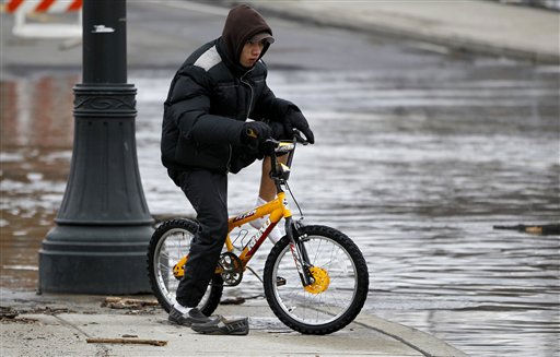 Douglas Pineda, 19, puts his socks and shoes back on after peddling through high waters on West Broadway in downtown Paterson, N.J., as the Passaic River overflowed, Sunday, March 13, 2011. The Passaic River crested overnight following a severe storm that hit the northern New Jersey region. &#40;AP Photo&#47;Julio Cortez&#41; <span class=meta>(AP Photo&#47; Julio Cortez)</span>