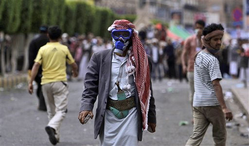 An anti-government protestor wearing a gas mask to avoid the effect of the tear gas fired by Yemeni police, holds stones during clashes between the factions in Sanaa, Yemen, Sunday, March 13, 2011.  Police on rooftops fired live rounds and tear gas on protesters Sunday, injuring more than 100 who were camping near Sanaa University calling for the Yemeni president to step down. Wielding clubs and knives, police and government supporters also attacked protesters from the ground, said Mohammed al-Abahi, a doctor in charge of makeshift hospital near the university. &#40;AP Photo&#47;Muhammed Muheisen&#41; <span class=meta>(AP Photo&#47; Muhammed Muheisen)</span>