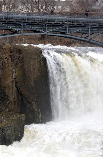"<div class=""meta ""><span class=""caption-text "">People are seen on a bridge at Great Falls as water from the swollen Passaic River pass over the falls, Sunday, March 13, 2011, in Paterson, N.J. The falls has been a place for residents looking to witness the intensity of the Passaic River following a severe storm that hit the northern New Jersey region. (AP Photo/Julio Cortez) (AP Photo/ Julio Cortez)</span></div>"