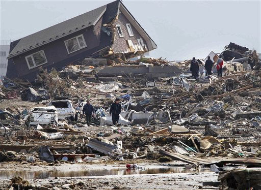 People walk in the rubble in Minamisanriku town, Miyagi Prefecture, northern Japan, Sunday, March 13, 2011, two days after a powerful earthquake-triggered tsunami hit the country&#39;s east coast. &#40;AP Photo&#47;The Yumiuri Shimbun&#41; JAPAN OUT, CREDIT MANDATORY <span class=meta>(AP Photo&#47; Anonymous)</span>