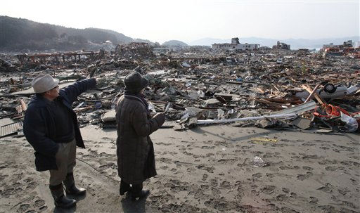 A hospital director, left, points at his hospital, center rear, that was engulfed in a tsunami at Minami Sanriku, northeastern Japan, on Sunday March 13, 2011, following Friday&#39;s catastrophic earthquake and tsunami. &#40;AP Photo&#47;Mainichi Shimbun, Satoru Ishi&#41; JAPAN OUT NO SALES ONLINE OUT MANDATORY CREDIT <span class=meta>(AP Photo&#47; Satoru Ishi)</span>