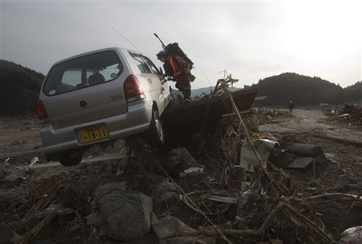 A Japanese rescue team member searches inside a car at the completely leveled village of Saito, in northeastern Japan, Monday, March 14, 2011. &#40;AP Photo&#47;David Guttenfelder&#41; <span class=meta>(Photo&#47;David Guttenfelder)</span>