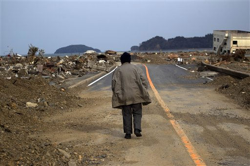 A Japanese earthquake and tsunami survivor walks alone on a road past the destroyed village of Saito, in northeastern Japan, Monday, March 14, 2011. &#40;AP Photo&#47;David Guttenfelder&#41; <span class=meta>(Photo&#47;David Guttenfelder)</span>
