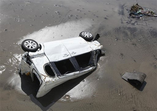 "<div class=""meta image-caption""><div class=""origin-logo origin-image ""><span></span></div><span class=""caption-text"">A car lies in the sand of the seaside town of Toyoma, northern Japan, as residents began to clear debris from their homes Monday, March 14, 2011, three days after a giant quake and tsunami struck the country's northeastern coast. (AP Photo/Mark Baker) (Photo/Mark Baker)</span></div>"