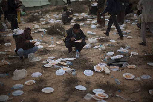 Men from Bangladesh, who used to work in Libya and fled the unrest in the country, eat their food in a refugee camp at the Tunisia-Libyan border, in Ras Ajdir, Tunisia, Monday, March 14, 2011. More than 250,000 migrant workers have left Libya for neighboring countries, primarily Tunisia and Egypt, in the past three weeks. &#40;AP Photo&#47;Emilio Morenatti&#41; <span class=meta>(AP Photo&#47; Emilio Morenatti)</span>
