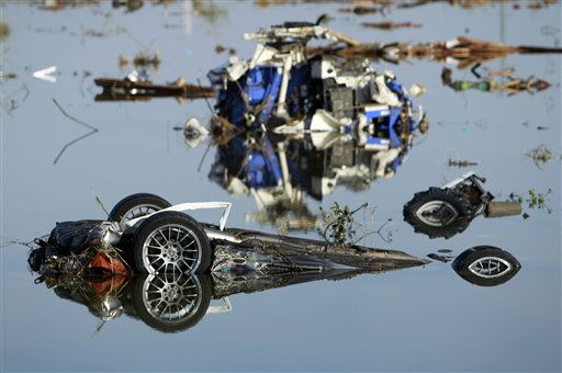 A wrecked sports car sits in flood waters, Monday, March 14, 2011, in Soma city, Fukushima prefecture, Japan, three days after a massive earthquake and tsunami struck the country&#39;s north east coast. &#40;AP Photo&#47;Wally Santana&#41; <span class=meta>(Photo&#47;Wally Santana)</span>