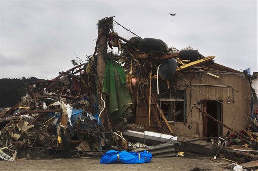 "<div class=""meta image-caption""><div class=""origin-logo origin-image ""><span></span></div><span class=""caption-text"">A body of a victim of the earthquake and tsunami lays wrapped in front of a house where recovery personnel found it in the leveled city of Minamisanriku, in northeastern Japan, Tuesday March 15, 2011. (AP Photo/David Guttenfelder) (AP Photo/ David Guttenfelder)</span></div>"