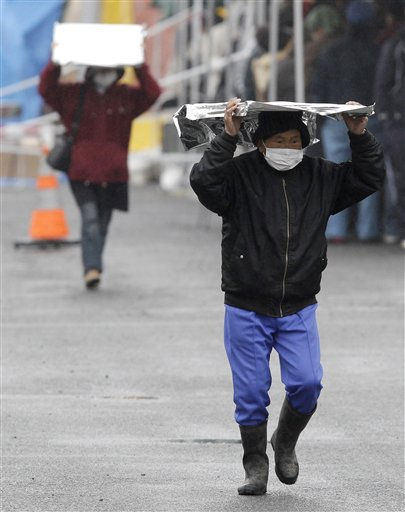 A man carries a heat blanket as he leaves a radiation emergency scanning centre in Koriyama, Fukushima Prefecture, Japan, Tuesday, March 15, 2011 four days after a giant quake and tsunami struck the country&#39;s northeastern coast. &#40;AP Photo&#47;Mark Baker&#41; <span class=meta>(AP Photo&#47; Mark Baker)</span>