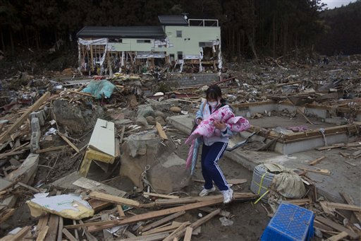 A young Japanese survivor of the earthquake and tsunami searches her family home for any belongings she can find in the leveled city of Minamisanriku, in northeastern Japan, Tuesday March 15, 2011. &#40;AP Photo&#47;David Guttenfelder&#41; <span class=meta>(AP Photo&#47; David Guttenfelder)</span>
