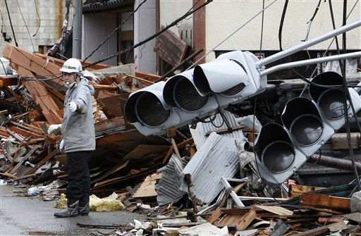 A construction laborer controls the traffic at a devastated area in Kesennuma, Miyagi Prefecture, northern Japan, Wednesday, March 16, 2011, after Friday&#39;s powerful earthquake-triggered tsunami hit Japan&#39;s east coast. &#40;AP Photo&#47;Shizuo Kambayashi&#41; <span class=meta>(Photo&#47;Shizuo Kambayashi)</span>