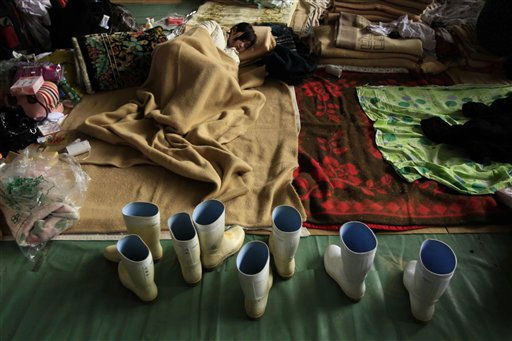 "<div class=""meta image-caption""><div class=""origin-logo origin-image ""><span></span></div><span class=""caption-text"">A youngster rests in a school gymnasium being used as a center for people to stay at whose homes were damaged by the tsunami in Ofunato, Japan, Wednesday, March 16, 2011. Two search and rescue teams from the U.S. and a team from the U.K. with combined numbers of around 220 personnel searched the town for survivors Wednesday to help in the aftermath of the earthquake and tsunami. (AP Photo/Matt Dunham) (AP Photo/ Matt Dunham)</span></div>"
