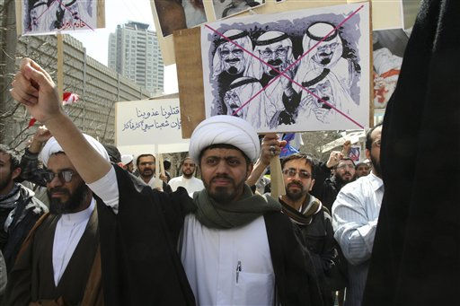 While a Shiite cleric chants slogan, a protestor holds a placard against Saudi King Abdullah, in a protest against Saudi and Bahraini leaders in front of the Saudi Embassy in Tehran, Iran, Thursday, March 17, 2011. Iran recalled its ambassador from Bahrain in protest to crackdowns on mainly Shiite protesters, state TV reported on Thursday. Also in Tehran, scores of foreign clerics and students angrily chanted against Saudi and Bahraini leaders after they gathered in protest at Bahrain and Saudi embassies on Thursday. (AP Photo/Vahid Salemi)