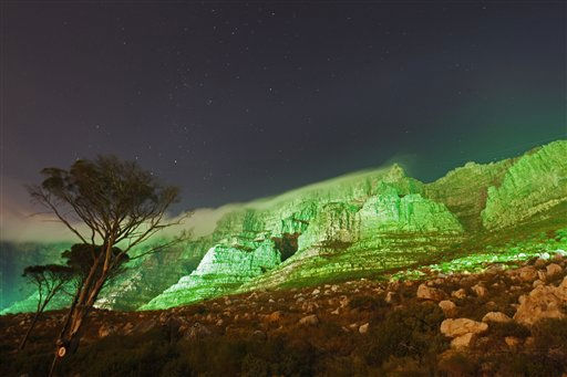 Table mountain is seen lit up in green, in a spectacular display to commemorate St Patrick's Day in Cape Town, South Africa, Thursday, March 17, 2011. (AP Photo/Schalk van Zuydam)