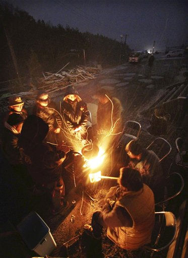 "<div class=""meta image-caption""><div class=""origin-logo origin-image ""><span></span></div><span class=""caption-text"">Survivors of Friday's earthquake and tsunami huddle around the open fire to keep warm out of doors in Minamisanriku town, Miyagi Prefecture, northern Japan, Thursday, March 17, 2011. (AP Photo/The Yomiuri Shimbun, Hirokazu Ono) JAPAN OUT, MANDATORY CREDIT (AP Photo/ Hirokazu Ono)</span></div>"