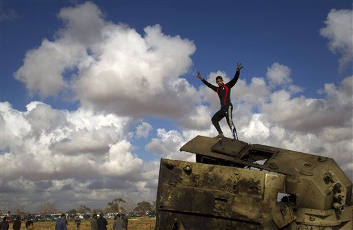 A Libyan boy reacts while standing on top of a destroyed military vehicle belonging to the forces of Moammar Gadhafi in the outskirts of Benghazi, eastern Libya, Sunday, March 20, 2011. &#40;AP Photo&#47;Anja Niedringhaus&#41; <span class=meta>(AP Photo&#47; Anja Niedringhaus)</span>