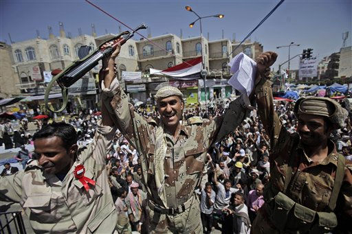Yemeni army officers react as they join anti-government protestors demanding the resignation of Yemeni President Ali Abdullah Saleh, in Sanaa,Yemen, Monday, March 21, 2011. Three Yemeni army commanders, including a top general, defected Monday to the opposition calling for an end to President Ali Abdullah Saleh&#39;s rule, as army tanks and armored vehicles deployed in support of thousands protesting in the capital. With the defection, it appeared Saleh&#39;s support was eroding from every power base in the nation _ his own tribe called on him to step down, he fired his entire Cabinet ahead of what one government official said was a planned mass resignation, and his ambassador to the U.N. and human rights minister quit. &#40;AP Photo&#47;Muhammed Muheisen&#41; <span class=meta>(AP Photo&#47; Muhammed Muheisen)</span>