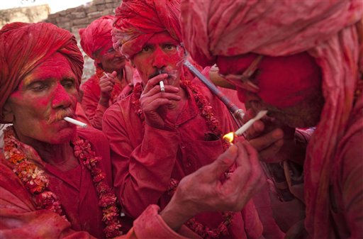Indian villagers covered in colored dye light cigarettes during Holi celebrations, the Hindu festival of colors in the village of Jaav 120 kilometers &#40;113 miles&#41; south of New Delhi, India, Monday, March 21, 2011. The festival marks the end of the winter season. &#40;AP Photo&#47;KevinFrayer&#41; <span class=meta>(AP Photo&#47; Kevin Frayer)</span>