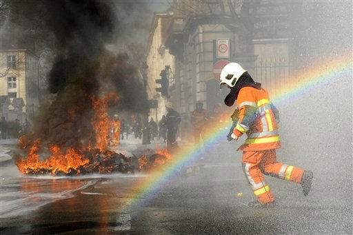 A Belgian firefighter runs through a rainbow during a demonstration in Brussels on Friday, March 25, 2011. Firemen demonstrated on Friday to protest against what they believe is bad management by their superiors.   <span class=meta>(&#40;AP Photo&#47;Geert Vanden Wijngaert&#41;)</span>