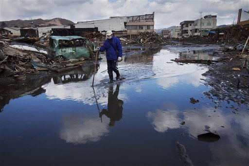 A Japanese walks through a flooded street in the tsunami and earthquake ravaged city of Kesennuma, northeastern Japan Sunday, March 27, 2011. The magnitude-9 quake off Japan&#39;s northeast coast March 11 triggered a tsunami that barreled onshore and disabled the Fukushima Dai-ichi nuclear power plant. &#40;AP Photo&#47;David Guttenfelder&#41; <span class=meta>(AP Photo&#47; David Guttenfelder)</span>