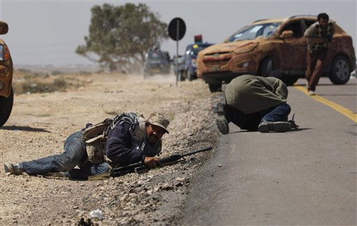 "<div class=""meta ""><span class=""caption-text "">Libyan rebels duck down as others take cover as they come under attack during an exchange of fire with pro Gadhafi forces along the frontline at the outskirts of Brega, Libya Monday, April 4, 2011. Libyan rebels pushed into the strategic oil town of Brega on Monday but came under fire from Moammar Gadhafi's forces, as a government envoy began a diplomatic push in Europe to discuss an end to the fighting. (AP Photo/Nasser Nasser) (AP Photo/ Nasser Nasser)</span></div>"