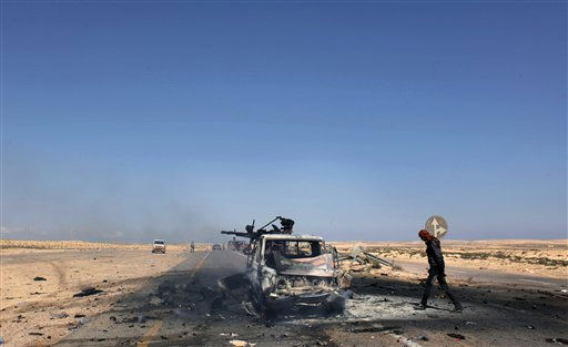 "<div class=""meta image-caption""><div class=""origin-logo origin-image ""><span></span></div><span class=""caption-text"">A Libyan rebel inspects one of two destroyed military vehicles of pro-Gadhafi forces that rebels claim were targeted by a NATO strike along the front line near Brega, Libya Tuesday, April 5, 2011. Libya's rebel forces are looking more effective on the front and even scrapping back some of the territory lost to Moammar Gadhafi's army, but the rag tag fighters are still a long way from being able to march to Tripoli. (AP Photo/Nasser Nasser) (AP Photo/ Nasser Nasser)</span></div>"