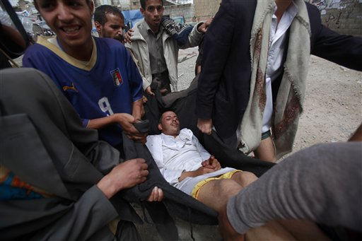 "<div class=""meta ""><span class=""caption-text "">Anti-government protestors carry an injured demonstrator in a blanket to a field hospital during clashes in Sanaa,Yemen, Tuesday, April 5, 2011. Opposition parties in Yemen have urged the international community, regional powers and human rights groups to help stop the bloodshed in their country. (AP Photo/Muhammed Muheisen) (AP Photo/ Muhammed Muheisen)</span></div>"