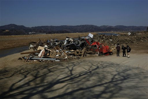 Survivors walk past some destroyed cars in Ishinomaki, Miyagi Prefecture, northern Japan Tuesday, April 5, 2011. &#40;AP Photo&#47;Vincent Yu&#41; <span class=meta>(AP Photo&#47; Vincent Yu)</span>