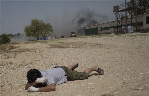 A man lies on the ground  as smoke rises from an explosion of a mortar shell fired by Palestinians militants from Gaza Strip in Kibbutz Nir Oz on Israel Gaza Border, southern Israel, Friday, April 8, 2011. Israeli aircraft and ground forces struck Gaza on Friday, killing two Hamas gunmen and three civilians in a surge of fighting sparked by a Palestinian rocket attack on an Israeli school bus the day before. Hamas said the rocket attack was retaliation for the killing of three fighters in an airstrike earlier in the week. &#40;AP Photo&#47;Ariel Schalit&#41; <span class=meta>(AP Photo&#47; Ariel Schalit)</span>
