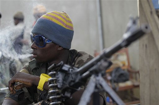 A soldier allied with Alassane Ouattara smokes a cigarette as he mans a machine gun along the roadside in the Youpougon neighborhood of Abidjan, Ivory Coast, Sunday, April 10, 2011. Human Rights Watch, in a report obtained by The Associated Press late Saturday, called on Alassane Ouattara to investigate and prosecute abuses by his forces and those supporting his rival, strongman Laurent Gbagbo. &#40;AP Photo&#47;Rebecca Blackwell&#41; <span class=meta>(AP Photo&#47; Rebecca Blackwell)</span>