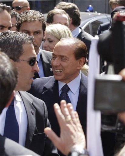 Italian Premier Silvio Berlusconi, center, flanked by his bodyguards, smiles as he speaks to his supporters outside Milan&#39;s courthouse where he attended his trial on tax fraud charge, Italy, Monday, April 11, 2011. Berlusconi says attending a hearing of his tax fraud trial in Milan was a waste of time and resources, accusing prosecutors of having no case against him. Berlusconi made a rare appearance in the courthouse Monday as dozens of supporters and political allies gathered outside. As he left after about two hours, Berlusconi greeted them, some with balloons saying &#34;Silvio, resist!&#39;&#39;  &#40;AP Photo&#47;Luca Bruno&#41; <span class=meta>(AP Photo&#47; Luca Bruno)</span>